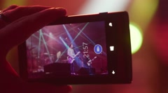 Person filming with mobile phone at open air rock festival - stock footage
