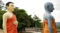 Pan from a group walking buddhas behind the World's tallest walking  Buddha Stock Footage