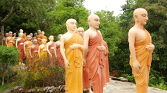 Pan from a group walking buddhas Stock Footage