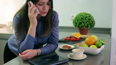 Angry businesswoman talking on cellphone in the kitchen, steadycam shot Stock Footage