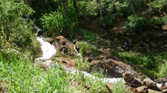 Pan from Waterfall to people at the road in Sabaragamuwa region, Sri Lanka Stock Footage