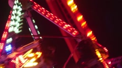 Large swinging ride in motion with people screaming at night - stock footage