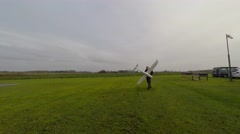 Man with airplane walking in a green landscape - follow shot Stock Footage