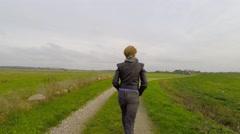 Woman walking in a green landscape - follow shot Stock Footage