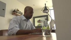An African American man works from home on a laptop. - stock footage