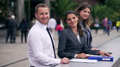 Businesspeople smiling to the camera on public square Stock Footage