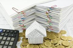 house on pile of gold coin with calculator - stock photo