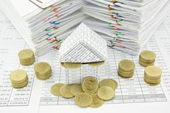 Stock Photo of house with pile of gold coin overload