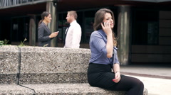 Businesswoman sitting on stone bench and talking on cellphone Stock Footage