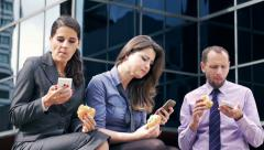 Businesspeople eating sandwiches and using cellphones Stock Footage