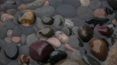 Water rising and falling over pebbles Stock Footage