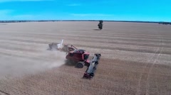 Tractor towing chaser bin peeling off from combine harvester - stock footage