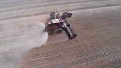 Panning aerial shot of harvester emptying into chaser bin - stock footage
