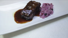 Veal candied black beer sauce with red fruits rice. Stock Footage