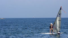 Windsurfer riding the waves into laguna blue sea waters Stock Footage
