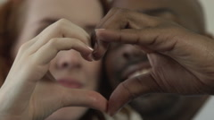 An interracial couple form a heart with their hands, kiss. Stock Footage