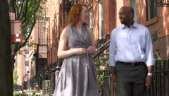 A happy interracial couple walk up the street - stock footage