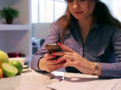 Woman typing sms and eating healthy breakfast at home Stock Footage