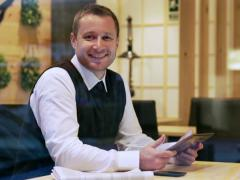 Man in the restaurant smiling to the camera and using tablet, steadycam shot - stock footage