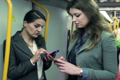 Businesswomen riding on metro and using cellphones, steadycam shot Stock Footage