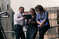Happy businesspeople looking on tablet and talking Stock Footage