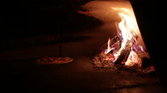 Pizza oven roasted by the fire Stock Footage