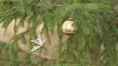decorative star an ball hanging in christmas tree - stock footage