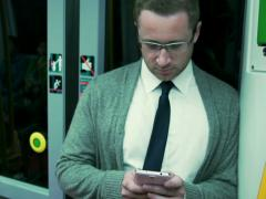Man riding on subway and texting on smartphone, steadycam shot Stock Footage