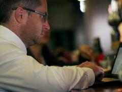 Businessman working on laptop in the pub, steadycam shot Stock Footage