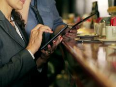 Businesswoman typing on tablet in the pub, steadycam shot Stock Footage