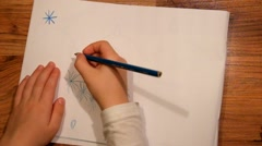 Close up view to drawing of child handr. Drawing of blue star with pencil. Stock Footage