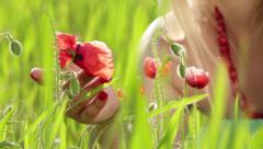 Girl lovely touching poppy flowers in green field - stock footage