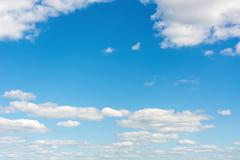 cumulus clouds in a bright blue sky. - stock photo