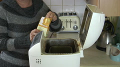 A packet of ready mix ingredients is poured into a bread maker. Stock Footage