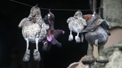 Toys hanging on a wire inside burnt building - stock footage