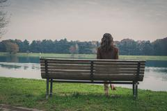 Beautiful young woman sitting on a bench in a city park Stock Photos