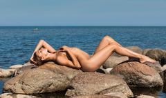 Beautiful young  nude woman by the sea Stock Photos