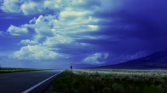 Indigo storm clouds over lonely road with prairie grass and mountain Stock Footage