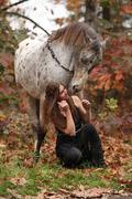pretty woman with appaloosa horse in autumn - stock photo