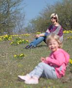 Mother and her daughter sitting and relaxing in the nature with yellow flowers - stock photo
