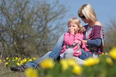 Mother and her daughter relaxing in the nature with yellow flowers Stock Photos