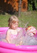 Little blonde girl playing in a water-filled kiddie pool - stock photo