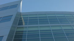 ESTABLISHING SHOT OF MODERN GLASS AND METAL OFFICE BUILDING EXTERIOR Stock Footage