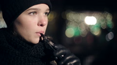 Teenager girl in the evening on the street smoking electronic cigarette. Stock Footage