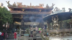 Longshan Temple - Woman bows at golden cauldron Stock Footage