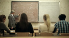 Group of students in a classroom, listening as their teacher holds a lecture. Stock Footage