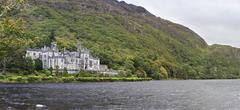 Kylemore Abbey in mountains on the lake. - stock photo