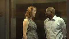 A happy interracial couple get into an elevator, chatting - stock footage