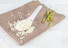 Rice grain in white spoon on a napkin Stock Photos