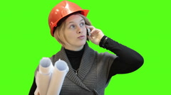 Engineer in hardhat holds blueprints, talks with phone, green screen background Stock Footage
